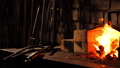 Closeup of a blacksmith fanning the flames of the furnace, using the tools prevents embers, sparks 40514350