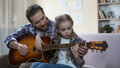 Father teaching daughter to play guitar at home,  40535133