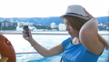 Woman in hat makes selfie bay with yachts. Background is the town of Cremea 40560511