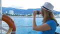 Woman in hat makes selfie bay with yachts. Background is the town of Cremea 40560514