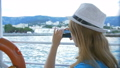 Woman in hat makes selfie bay with yachts. Background is the town of Cremea 40560518