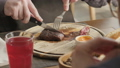 the man in the restaurant with a knife cuts steak of marble beef, grilled. Serving on a wooden Board 40651874