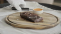 the man in the restaurant with a knife cuts steak of marble beef, grilled. Serving on a wooden Board 40651903