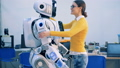Young woman is coming to a human-like robot, they are hugging and talking 40754189