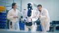 Human-like robot is going through a fixing procedure hold by two technicians 40754230
