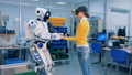 Robotic humanoid is putting its hands onto the hands of a young woman 40754231