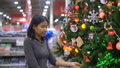 Woman is touching christmas tree decorations 40821582