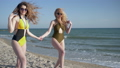 summer morning, cheerful girlfriends in swimsuit and sunglasses have fun while walking 41541631