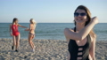 Portrait of cheerful female in glasses and bathing suit on background of Friends on beach 41541632