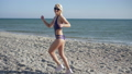 holiday at sea, girl with beautiful figure in swimsuit and sneakers runs and turns on Embankment 41541634