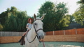 Young happy girl sits on a pretty white horse on the area. FullHD 41553347