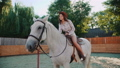 Young happy girl sits on a pretty white horse on the area. FullHD 41553348