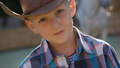 Portrait of little handsome cowboy looks and poses at camera. FullHD 41553349