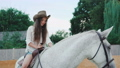 Young happy girl poses on a pretty white horse on the area. FullHD 41553358