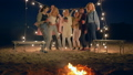 company of young people dancing and singing near bonfire on beach in lighting of garlands 41563480