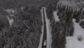 Car driving on winter country road in snowy forest, aerial view from drone 41574612