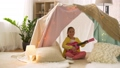 girl with toy guitar playing in kids tent at home 41924536