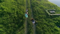 Aerial video, cheerful kid with teenager girls with colored ribbons in hands walk at glade along 42169280
