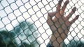 Female hand moving along the surface of grid. Arm of young woman touching metal wire fence. Girl 42303677