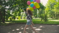 Happy, playful girl poses with colourful balloons on the walk in sunny park 42408950