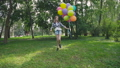 Happy, playful girl jumps with colourful balloons on the walk in sunny park 42408951