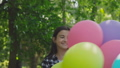 Happy, playful girl poses with colourful balloons on the walk in sunny park 42408952
