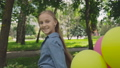 Happy, playful girl poses with colourful balloons on the walk in sunny park 42408953