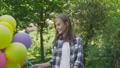 Happy young girl rejoicing with colourful balloons in a park 42408955