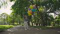 Happy, playful girl rejoices with colourful balloons on the walk in sunny park 42408956