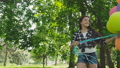 Happy, playful girl poses with colourful balloons on the walk in sunny park. FullHD 42408957