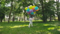 Happy, playful girl poses with colourful balloons on the walk in sunny park 42408961