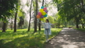 Happy, playful girl poses with colourful balloons on the walk in sunny park 42408963