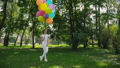 Happy young girl poses in the green sunny park and holds colourful balloons 42408965