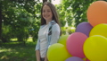 Happy, playful girl poses with colourful balloons on the walk in sunny park 42408967