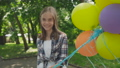 Happy young girl rejoicing with colourful balloons in a park. FullHD 42408968