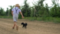 little boy and puppy running around and playing in an apple garden, slow motion 42452343