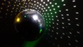 Mirror balls rotate and reflect lights of projectors breaking through smoke at night club 42569204
