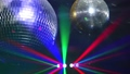 Mirror balls rotate and reflect lights of projectors breaking through smoke at night club 42569209