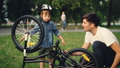 Little boy is spinning bicycle wheel and pedals while his father is talking to him on lawn in park 42602712