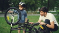 Curious child wearing helmet is spinning bicycle wheel and pedals while his father is talking to him 42602726