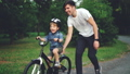 Slow motion of laughing child cycling in park with careful father who is teaching him to ride 42602728
