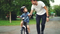 Slow motion of loving dad teaching his adorable son to ride bicycle in park holding bike and talking 42602729