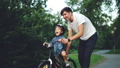 Slow motion of happy young man loving father teaching his child to cycle in green park in summer 42602730