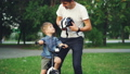 Slow motion of loving dad talking to his little son then putting protective bicycle helmet on his 42602731