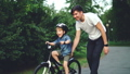 Slow motion of excited boy riding bicycle and laughing while his careful father is helping him 42602735