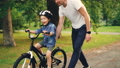 Slow motion of cheerful guy caring father teaching his small son to ride bicycle in park. Cute boy 42602738