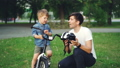 Caring father is holding bicycle helmet and talking to his adorable son explaining safety 42602741