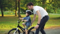Handsome young man loving father is teaching his small son to ride bicycle in park on summer day 42602742