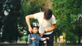 Caring father is putting safety helmet on his little son's head then teaching happy boy to ride 42602743