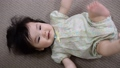 一個可愛的寶寶躺下,讓她的腳變得雜亂,0歲,一個女孩 42915239